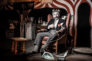 Image of clown sitting in chair.